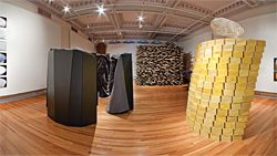 An overview of the Shelter: On Kindness exhibition at RMIT Gallery. On the left is LAB Architecture Studio's Safe-House. To the right is Gregory Burgess and Pip Stokes' yellow beeswax installation, Sense. March Studio's shelter is seen in the background.