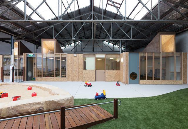 室内景观在仓库的倾斜屋顶和钢桁架下方展开。