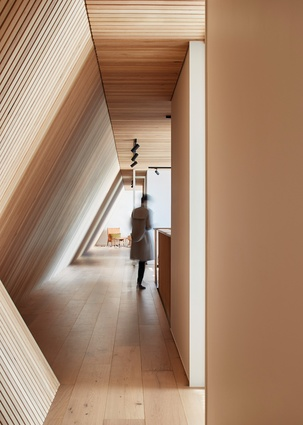 The result of envelope restrictions, the angular southern wall forms a timber-clad corridor, which connects the bedrooms and guest areas on the upper level.