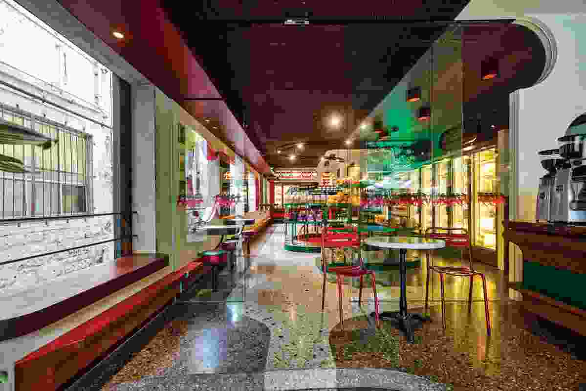 The grocer features green shelving and bar seating.