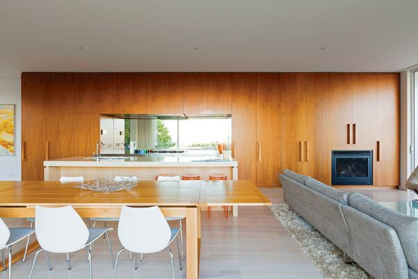 A stainless steel cooking zone is framed by the joinery and has a mirrored splashback that reflects a coastal view.