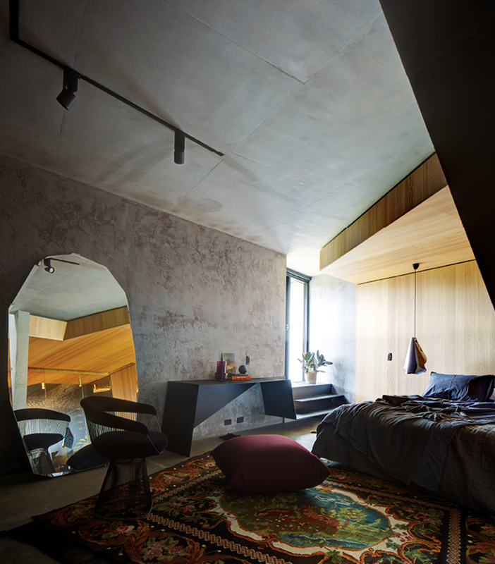 On the lower level, a cave-like guest bedroom appears to have been carved out of the hillside.