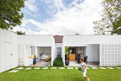 A gentle but dramatic transformation has taken place at the rear of a red brick home, with breezeblock walls creating outdoor rooms that open onto the yard.
