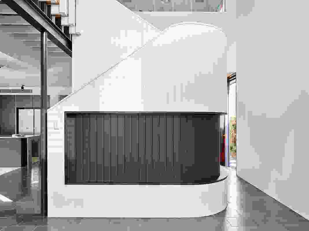 Wrapped in white vertical joint boards, the stair is a solid, sculptural object that divides living from dining spaces.