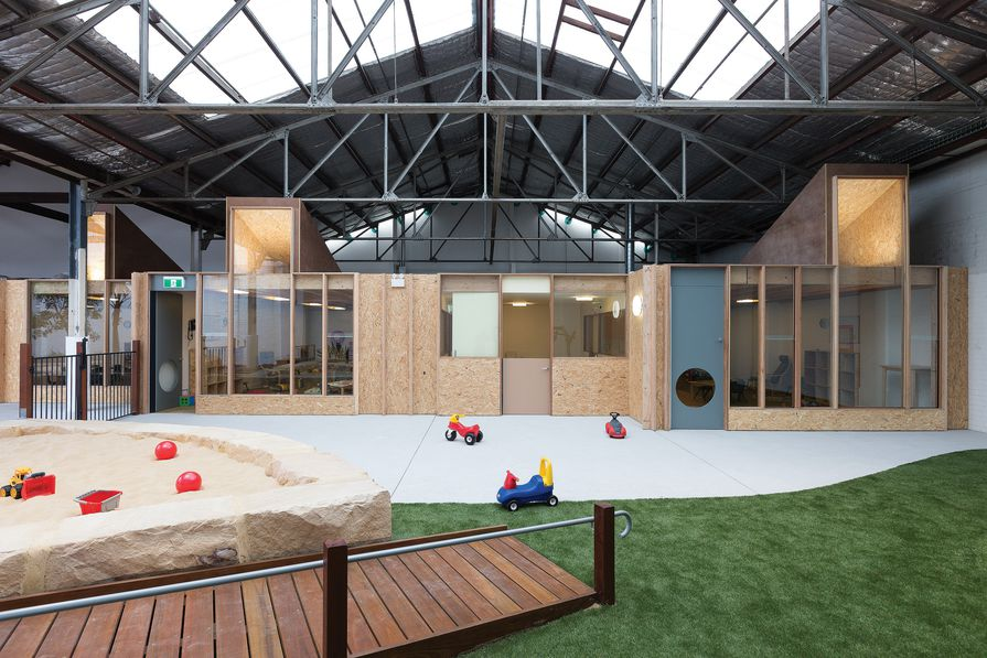 An indoor landscape unfolds beneath the pitched roofs and steel trusses of the warehouse.