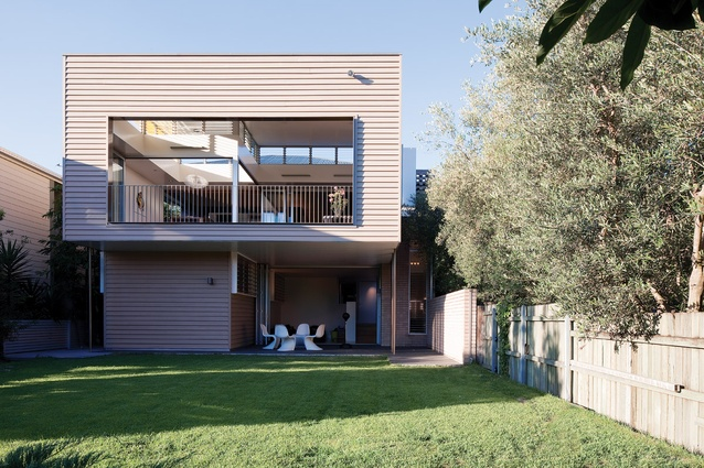 The rear elevation opens to a level patch of lawn, which conceals a twelve-thousand-litre water tank.