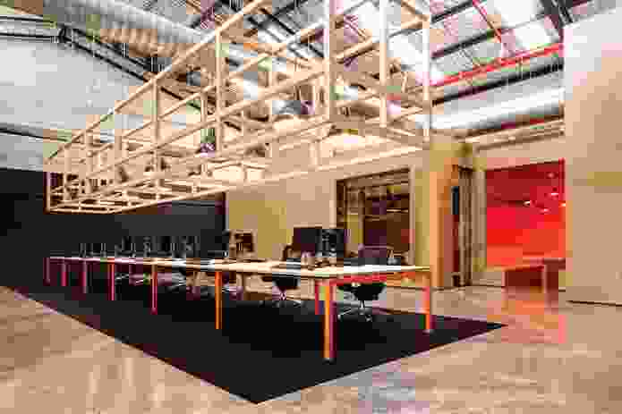 An open timber matrix is suspended above the central workstation.