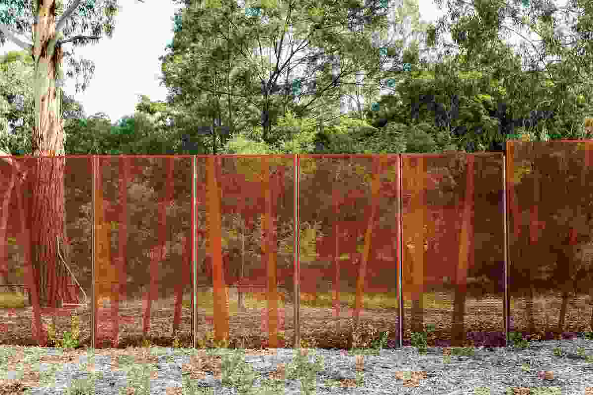 Abstracted tree trunk fence panels subtly reference the biological sciences while helping to protect the sensitive ecology of the reserve.