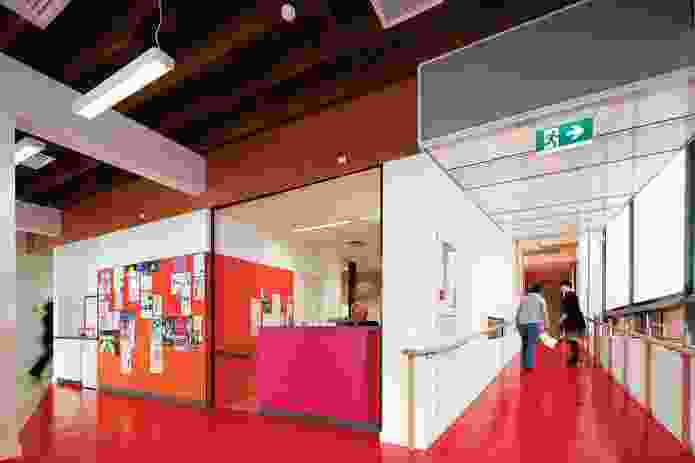 Women's Health and Family Services. Red vinyl flooring extends from the entry, past the plywood-clad staircase and into the group areas to the right.