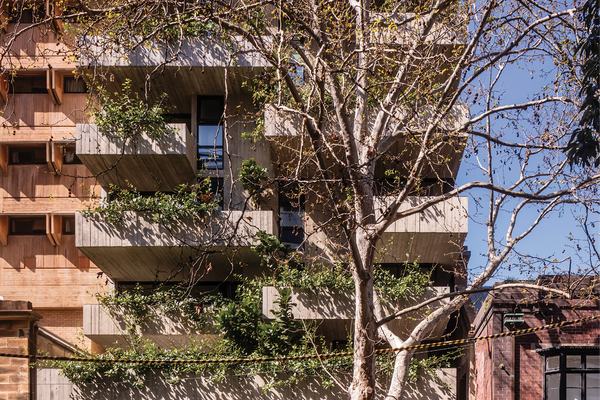 Located in the inner-Sydney suburb of Surry Hills, Woods Bagot's residential and retail building presents a memorable facade of staggered concrete forms and dense foliage.