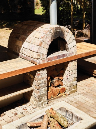 A brick fire pit and courtyard form the social heart of the home, tying the other spaces together.