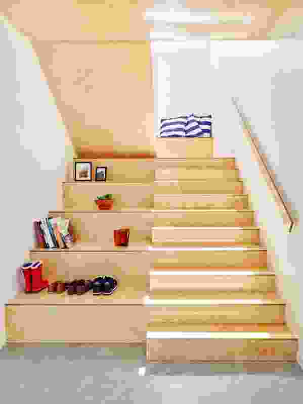 The plywood stair that leads up to bedrooms is designed not only for circulation, but also for play and display.