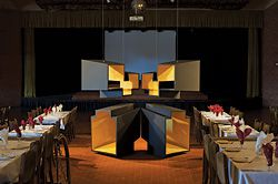 8 Workshop Architecture's Golden Memories in the empty dining room, amongst tables set for dinner.