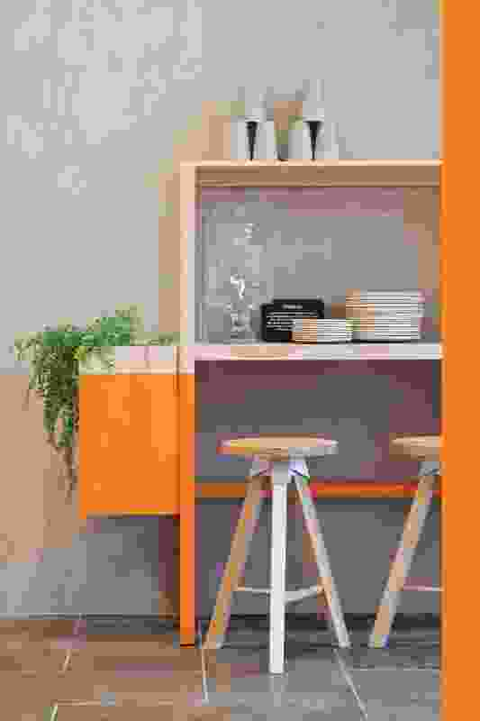Timber shelves have been partly painted in bright orange to add vibrancy to the eating areas.