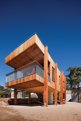 Clad in timber, the new elevated space shifts away from the original house.