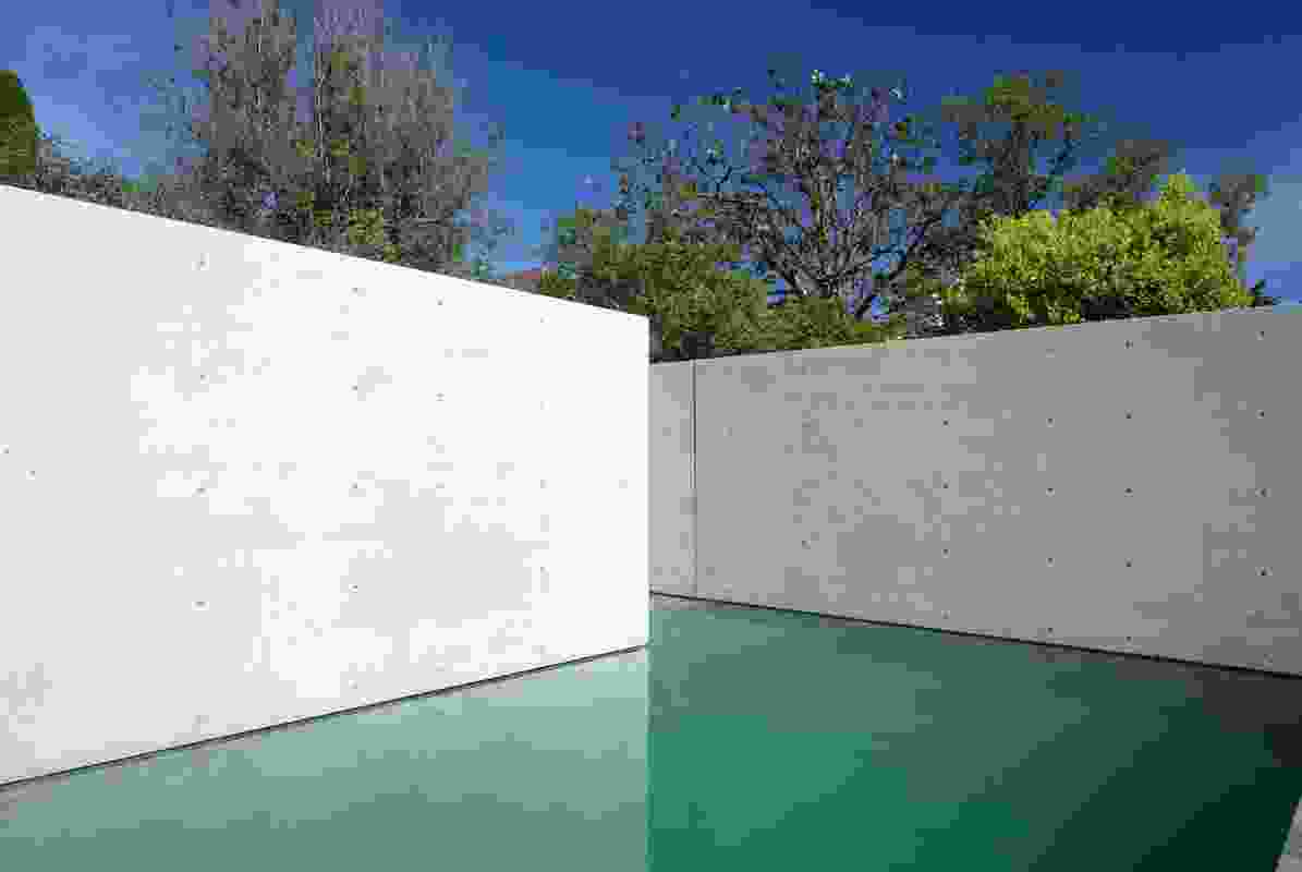 The backyard is wrapped in high, off-form concrete walls and features a Barragán-esque pool.