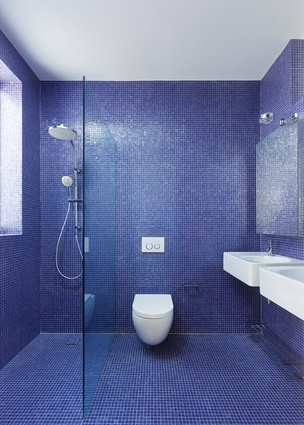 The use of colour in the bathrooms provides a playful note in an otherwise restrained material palette.