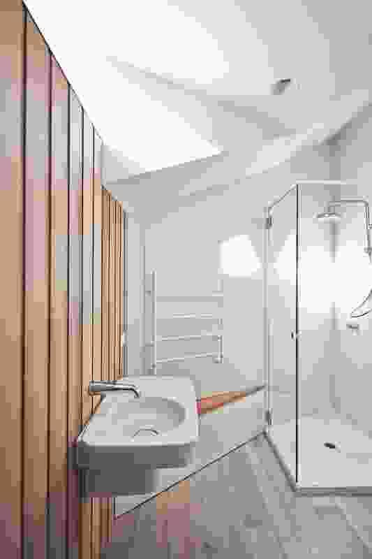 A full-width glazed roof light captures morning sun on the upper-level landing and bathroom.