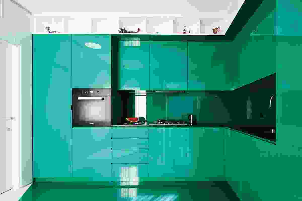 L-shaped green cabinetry defines the kitchen, with white banding maintained along the top to create an abstracted frieze.