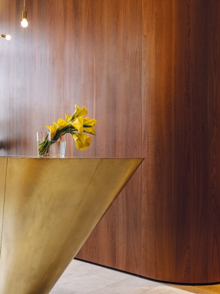 The kitchen island, appearing more like a brass monolith, was made by sculptor Morgan Shimeld.