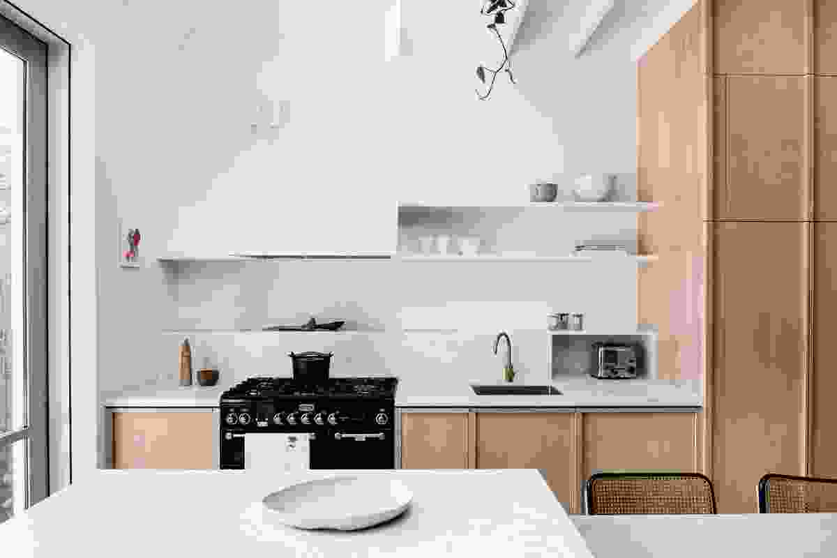 The kitchen is tucked beneath the stair, one of several tactics employed by the architects to maximize space. Artwork: Michael Georgetti.