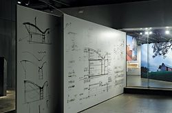 Drawings of the Bingie Point House, looking through the exhibition window towards an image of the Marie Short House.