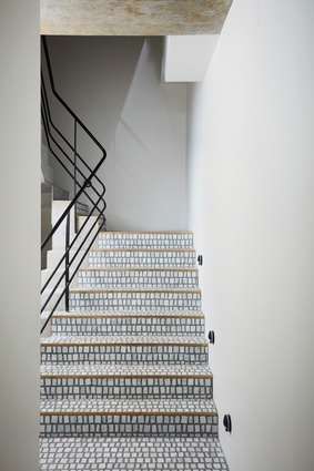 Visitors to the studio go through a tall steel door to a foyer leading to a staircase lined with small marble tiles and a lift.