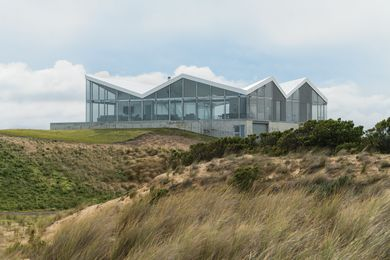 The house's concrete base rises above the dunes, as if it were a raft breasting waves.