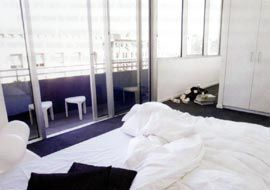A bedroom on the south end of the building, with a concrete balcony overlooking Collins Street.