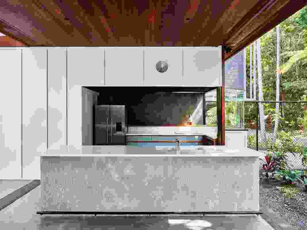 The threshold between garden and kitchen is tempered by slide- away doors.