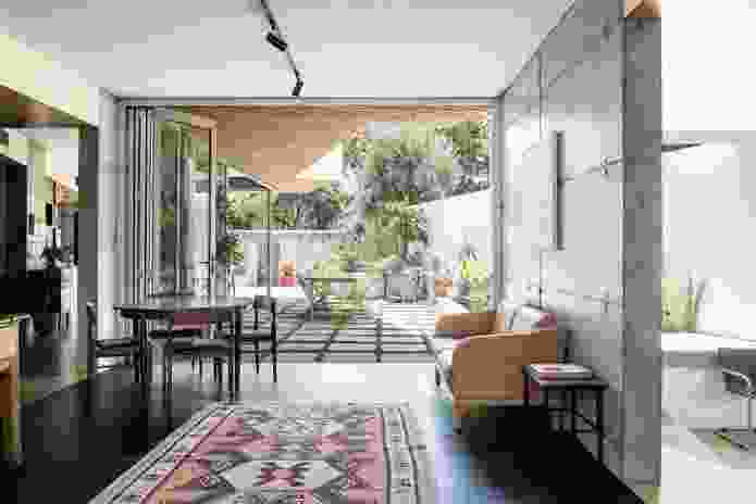 The second storey mass projects beyond the footprint of the ground floor, providing shade to the outdoor spaces. Artwork: Eveline Kotai.