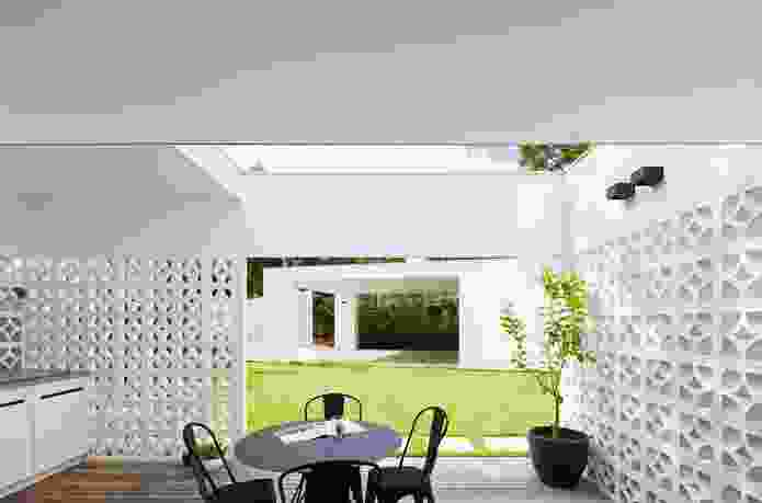 Breezeblock walls create outdoor rooms for various uses, a deck beyond the kitchen serving as an outdoor dining space.