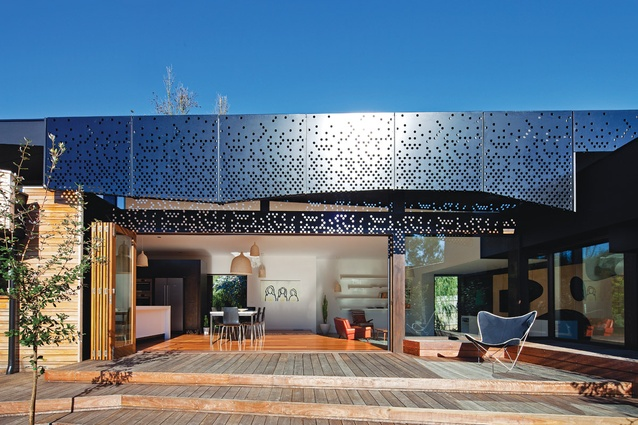 Perforated metal screens on the facades throw dappled light across the terraced decking.