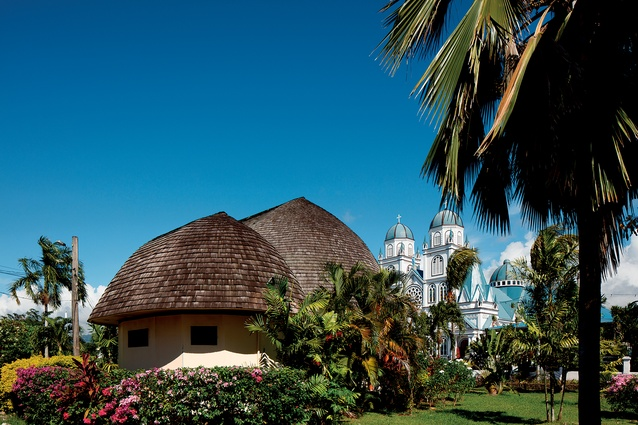 Samoa Cultural Village (front) and Mulivai Cathedral of the Immaculate Conception of Mary (back), both in Apia, Samoa.
