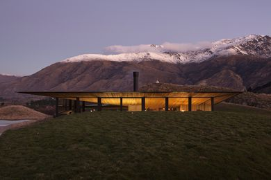 The home takes flight from the land against a backdrop of snow-capped mountains and rolling, grassy hills.