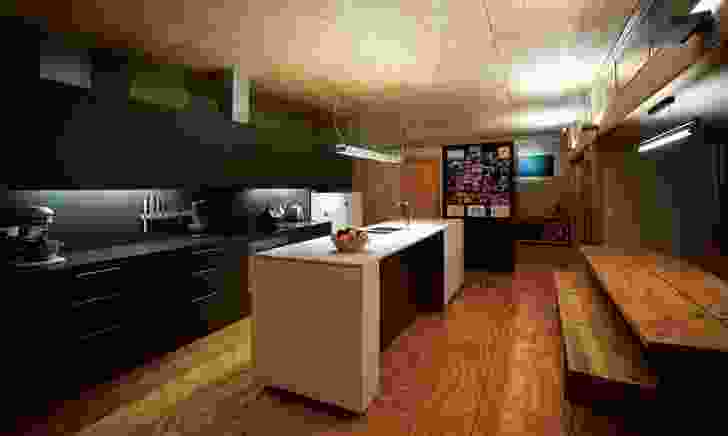 The houses share a similar material palette. Plywood panels on both the ceiling and floor give warmth to the kitchen.
