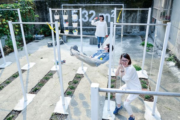 Steel horizontal bars serve as scaffolding for a variety of uses at the ParkUp community gathering site in Taipei, Taiwan designed by Plan b.