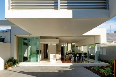 Overhanging masonry functions as both an  off-street double car park and an alfresco dining area.