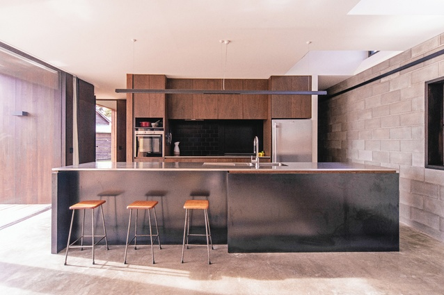 Mild steel plate lines the kitchen bench, offering a lustrous surface, while joinery and cladding are stained to match surrounding gum trees.