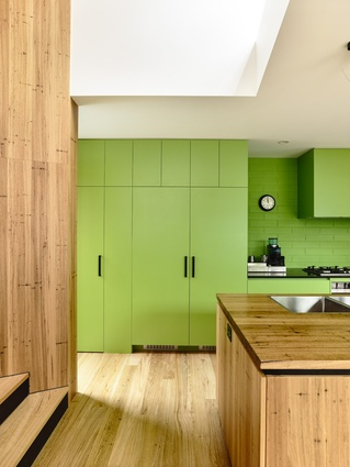 Bright green joinery an accent that contrasts with an otherwise neutral material palette.