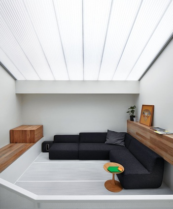 On the upper level, a translucent roof creates a large, open lightwell, with light penetrating through the perforated steel floor to the lower levels. Artwork: Liesl Pfeffer.