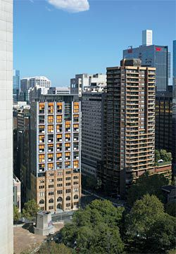 The northern facade overlooking Lang Park. The changing pattern of orange solar blinds animates the facades.