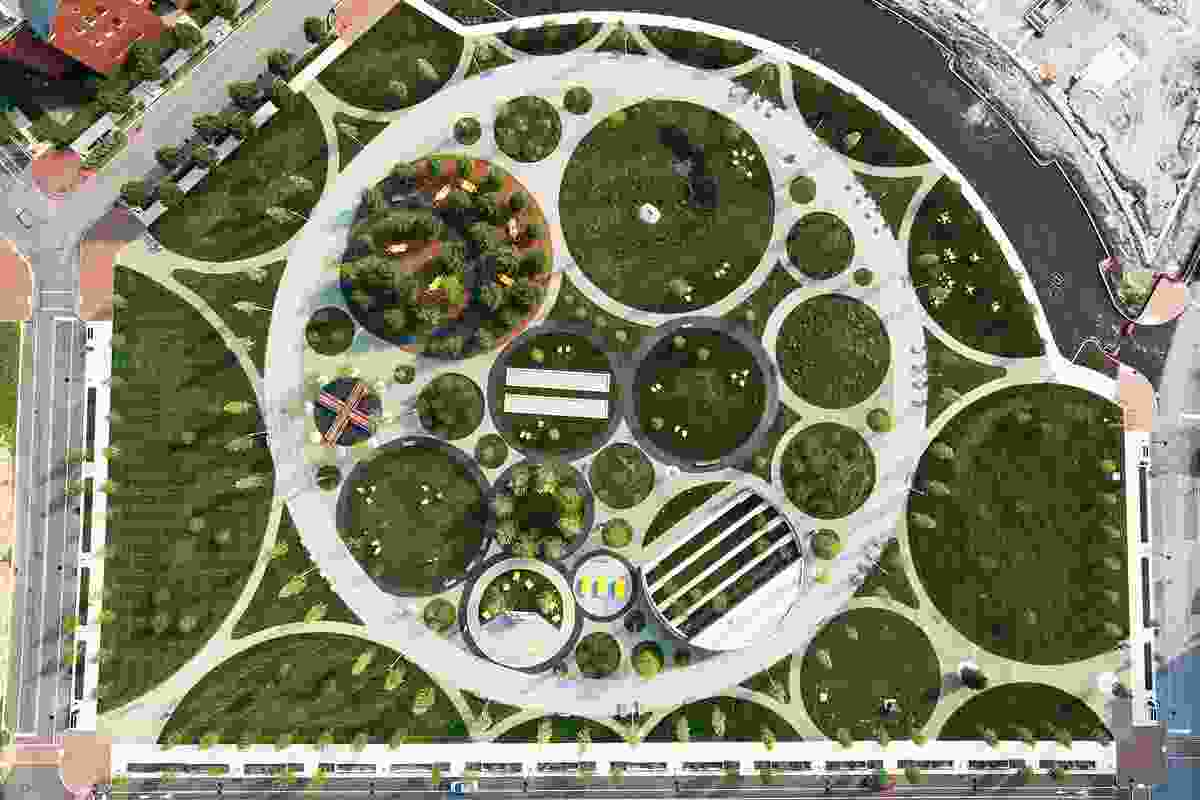 A social track organizes circulation and frames an immersive interior park featuring flowering meadows, a hammock grove, an outdoor amphitheatre, bocce courts and fitness stations at the Navy Yards Central Green.