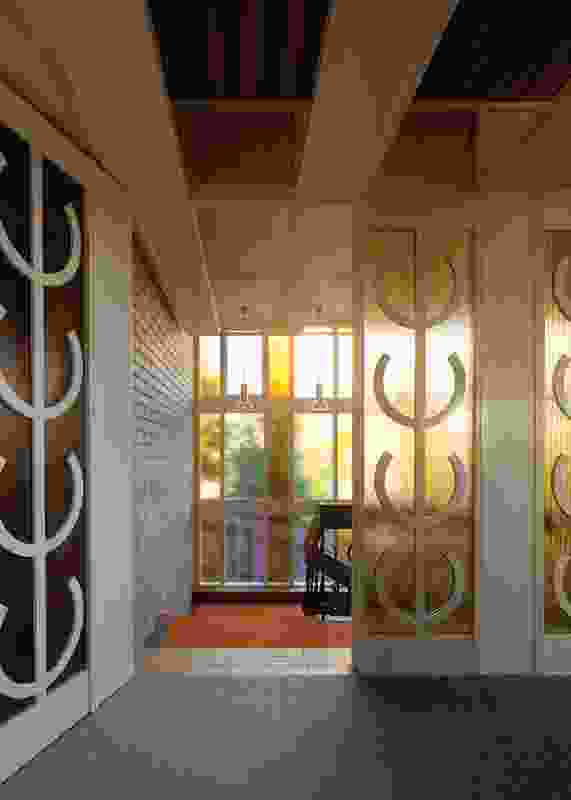 """A glass screen at the top of the entry stair displays the """"house motif"""" – a series of abstracted candelabras."""
