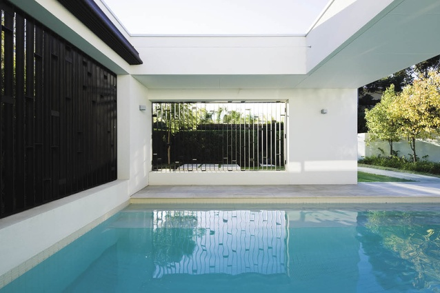 A semi-enclosed pool features black aluminium grilles, braced with fine plates that subtly shift in orientation, vertically and horizontally.