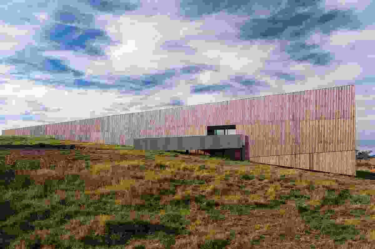 The geometric form of Marion Bay House is wrapped by a timber-clad wall that seems to disappear into the hill.
