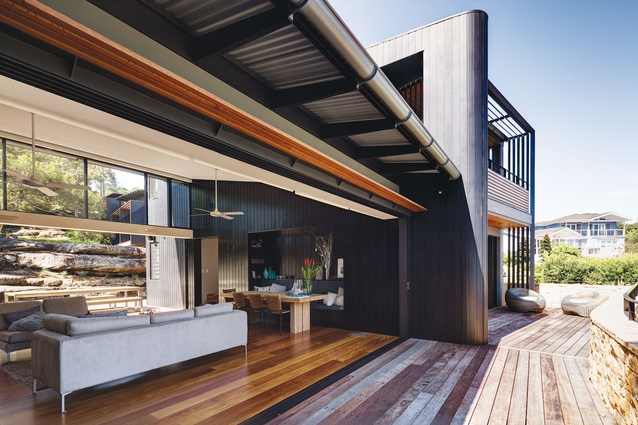 A timber-clad wall continues from the inside to the outside.