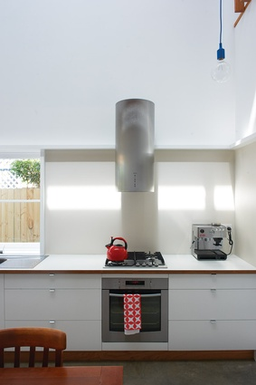 White and plywood keeps the compact kitchen fresh.