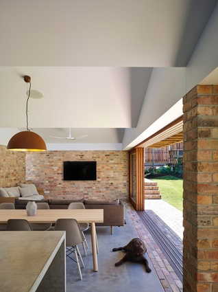 The exterior brick paving is flush with the interior's concrete floors, making the transition between indoor and outdoor spaces ambiguous.