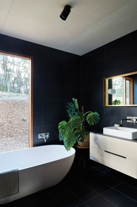 Moments of saturated colour rest on a base of neutral tones, such as the black porcelain tiles of the upper pavilion's bathrooms.